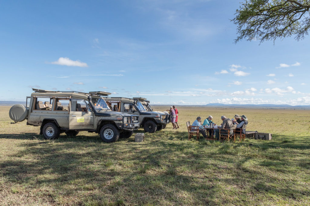 African Safaris in Kenya guests taking breakfast on safari with vehicles and guides